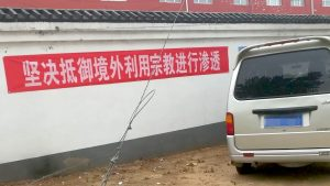 """A banner hanging on the wall, reading """"Resolutely Guard Against Overseas Infiltrations via Religious Means."""""""
