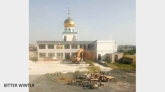 Excavator demolishing part of the mosque building with obvious Islamic characteristics