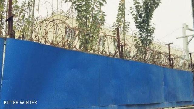 The outer wall is covered with blue steel plates. The top of the wall has been fitted with spiral-shaped barbed wire.