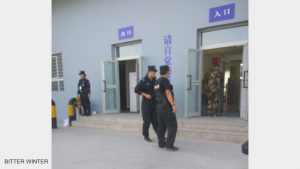 Police patrol and stand guard outside the re-education camp.