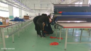 Workers adjust and test machines in a large factory.