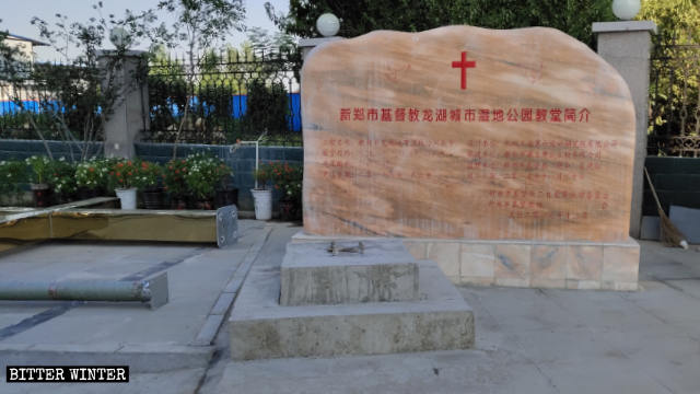 The discarded cross next to the introduction to Three-Self Longhu Urban Wetland Park Church in Xinzheng.