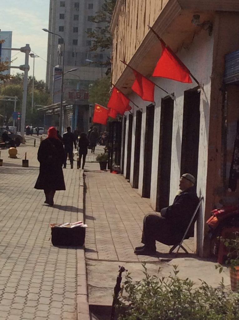 Basking in the shade of the Chinese red flag in Urumqi.