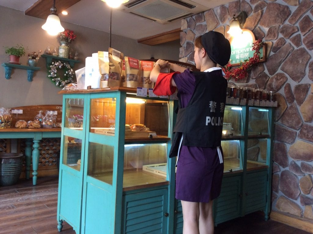 Everyone is drafted into the war on terror, even this young shop assistant, wearing her compulsory red armband and bullet proof vest. Summer 2017.