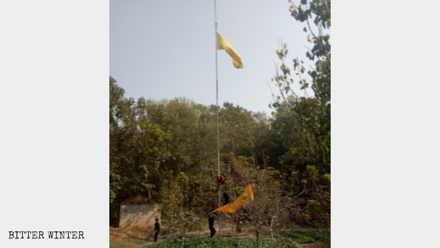 Government employees take down the temple's banners.