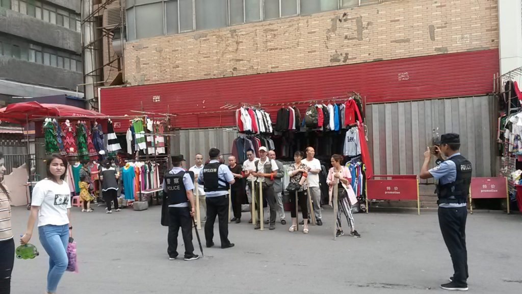 Urumqi back street traders being photographed by the community police following a 'weapons' drill. August 2018.