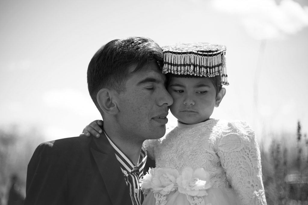 A man affectionately carries his daughter, dressed for a family celebration