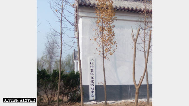 "The exterior wall of Hongshan Temple has been painted white. A sign reading ""Elderly Activity Center"" hangs on the exterior wall."