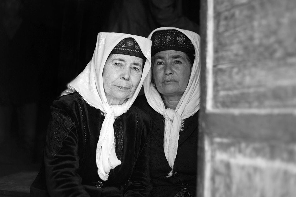 Two women of the Tajik minority snuggle together.