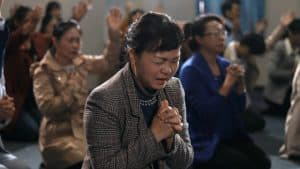 Believers at a house church are praying earnestly