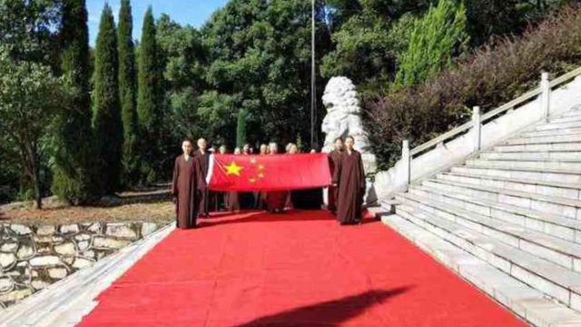 Monks at Wanshan Temple in Jiangxi's Lushan city attend a flag-raising ceremony.