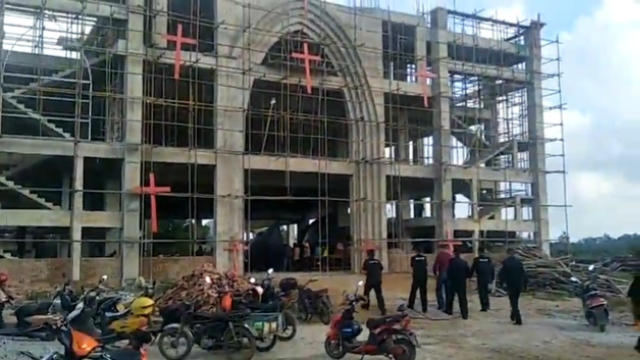 Personnel participating in the forced demolition enter the church.