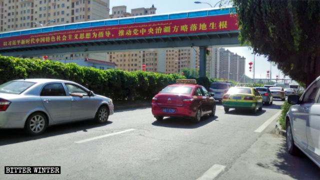 "A propaganda slogan poster in Xinjiang's Urumqi: ""Promote the full implementation of the Party Central Committee's strategy for governing Xinjiang,"" guided by Xi Jinping's thought."