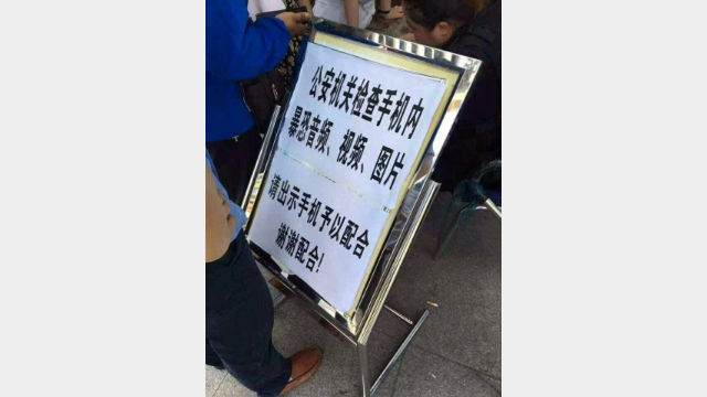 A warning sign at a border post in Xinjiang, informing that everyone crossing the border will have their mobile phones checked. (by Radio Free Asia reporter Qiao Long)
