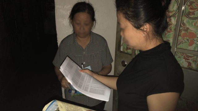 A government official visits a believer's home and registers her information.