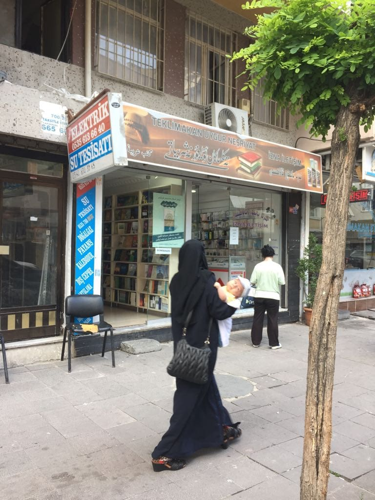 "A Uyghur ""widow"" passing a Uyghur bookstore in Istanbul."