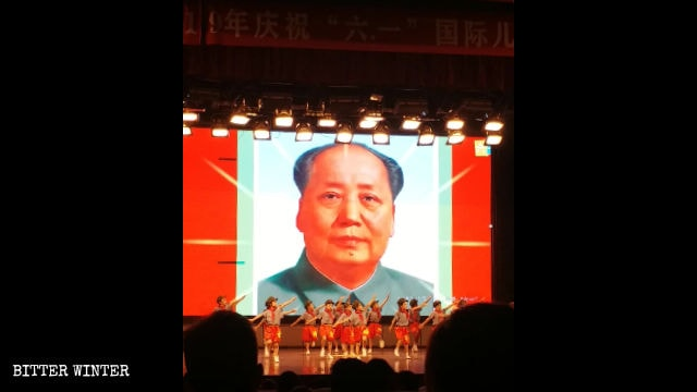 "Children at a ""red"" performance, staged in front of the portrait of Mao Zedong."