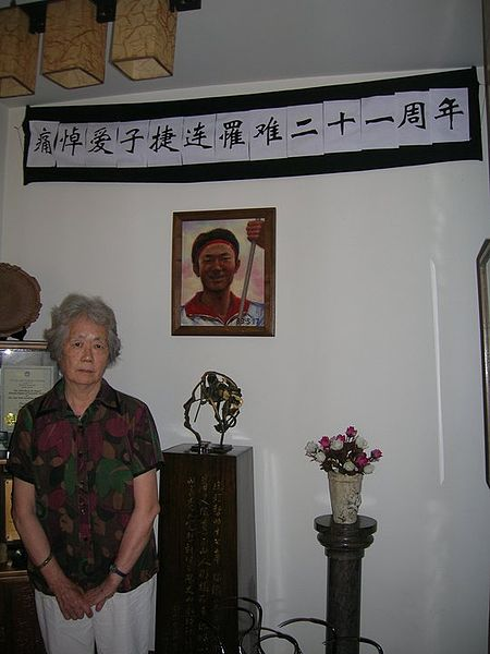 Ding Zilin with a portrait of his killed son, Jiang Jielian
