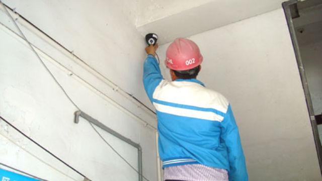 A worker is installing a surveillance camera.