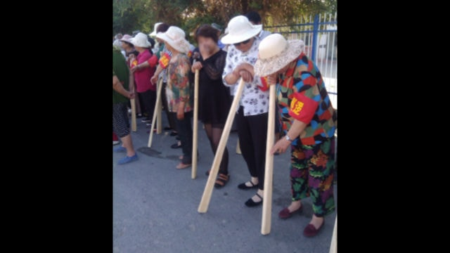 "People in a locality of Xinjiang are carrying wooden bats as they participate in ""counter-terrorism drills."""