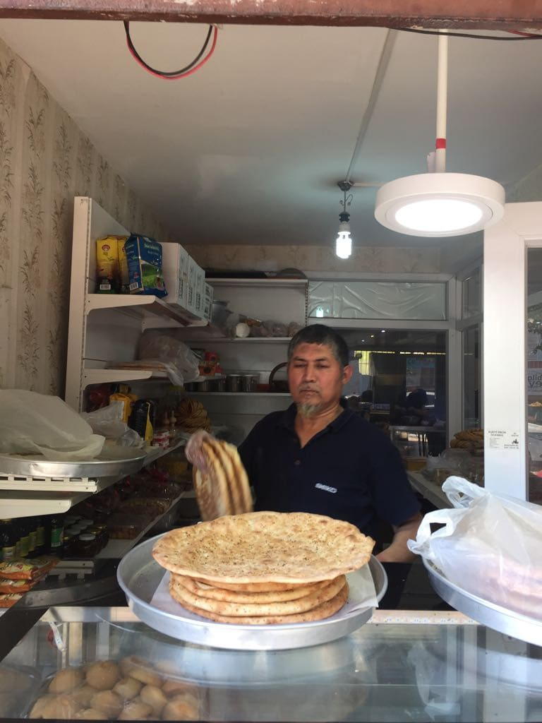 "This Kashgar baker proudly displays his piping hot ""naan"" bread fresh"