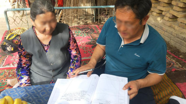 government official in Xinjiang asks an elderly woman to read the materials