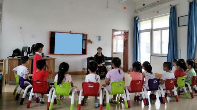 A kindergarten teacher is talking to children in a class.