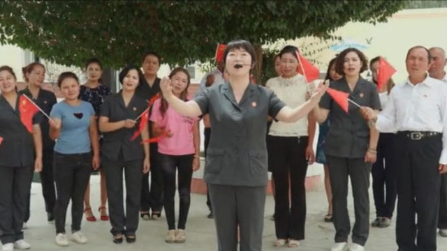 "A Han Chinese boss leads her Uyghur work unit in singing ""I love you China"""