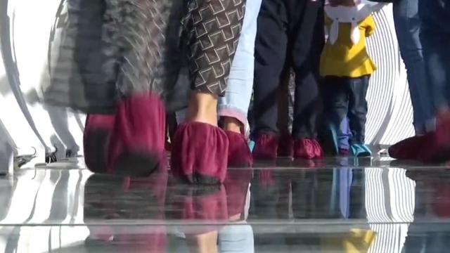 "Tourists wear overshoes as they traverse the bridge on specially programmed glass, which ""shatters"" and ""splinters"" under their feet."