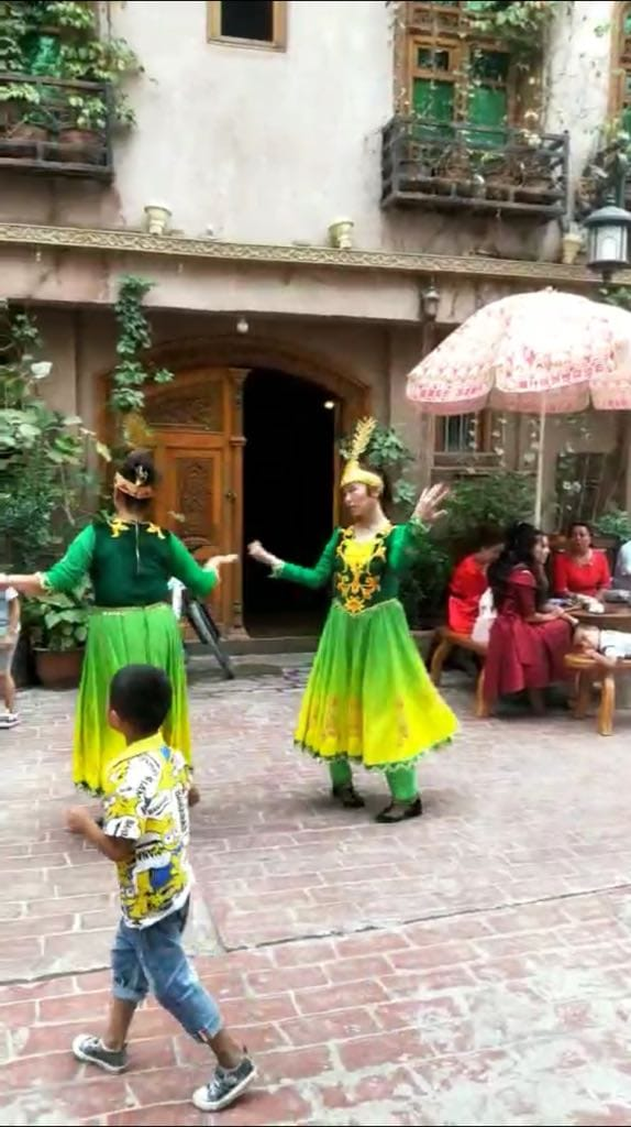 Looking very much unhappy, Uyghur girls are compelled to dance for Han tourists in Kashgar.