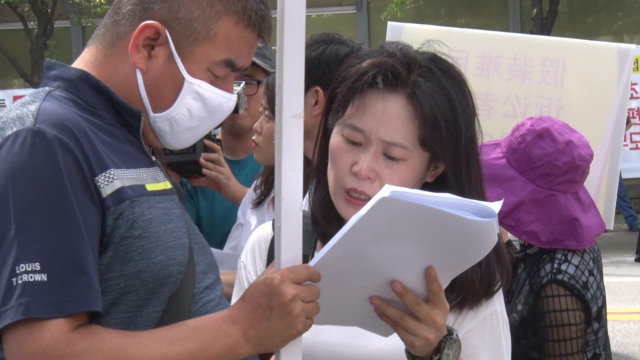 Ms. O Myung-ok is checking the manuscript with a relative of a CAG believer during the demonstration.