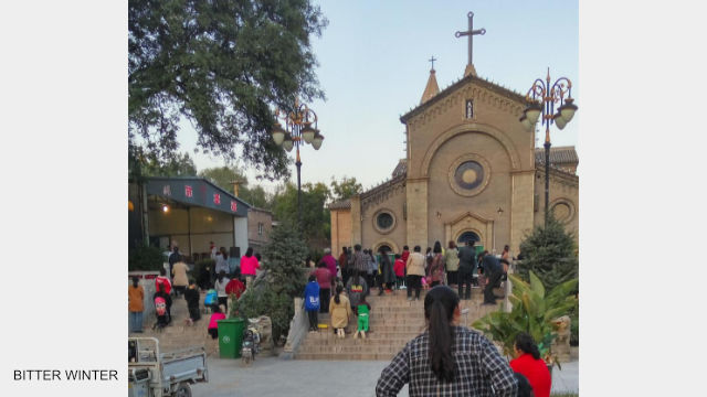 Believers gather at the meeting venue outside the church