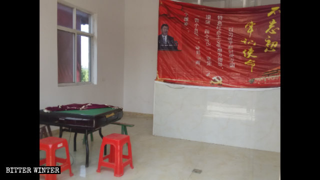 A banner with Xi Jinping portrait was put up on the wall facing two mahjong tables in what used to be a chanting hall.