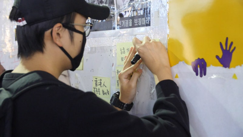 A rally participant writes blessings to Hong Kong people on the Lennon Wall.