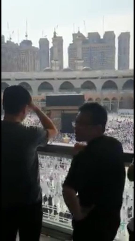non-Muslim Chinese tourists observing and photographing pilgrims in Mecca