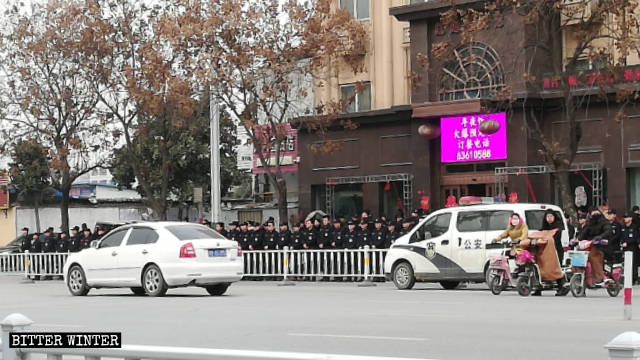 Special police officers standing in three rows to block the entrance in front of Haoyue Hotel.