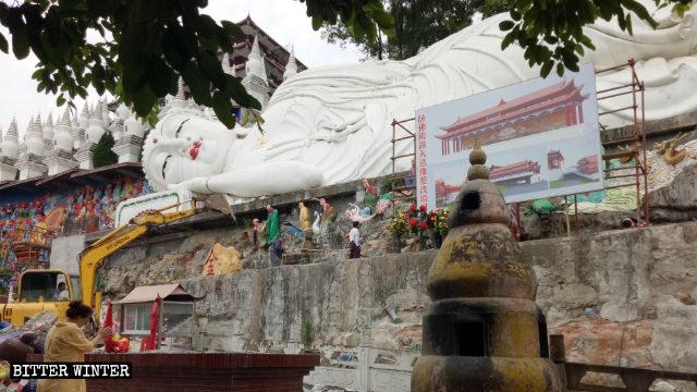 An excavator is demolishing 500 Arhat statues around the reclining Buddha.