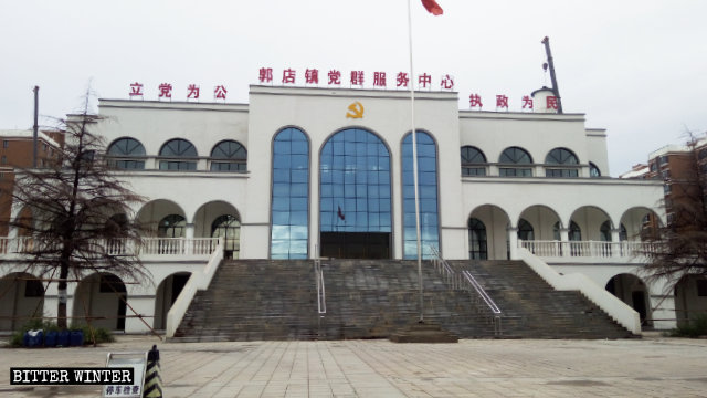 "The sign reading ""Guodian Town Service Center for Party Members and Masses"" was displayed above the entrance to a mosque in Guodian town, Henan, transformed into a government agency building."