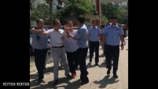 Police officers are taking away a Zhongxin Church co-worker.