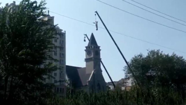 A crane is taking down the statue of Jesus from the bell