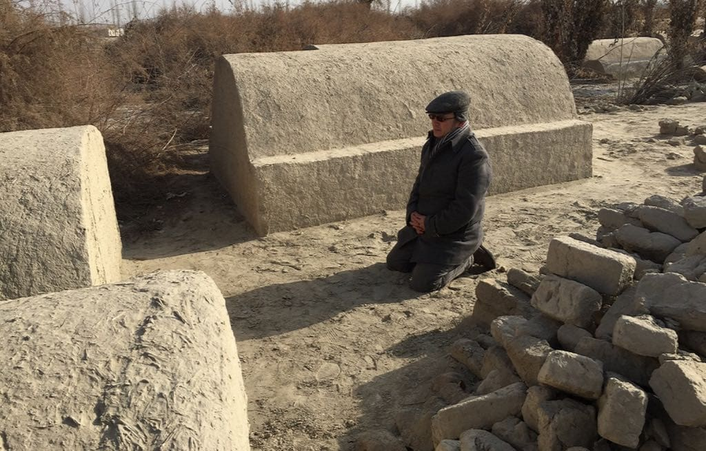 … but this picture of Aziz kneeling in front of his family grave in 2012, before it was destroyed, proves that the CCP propaganda is lying