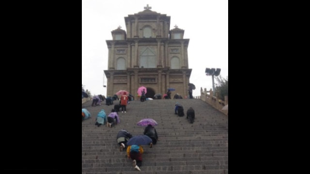 Believers climbed on their knees to the Gate of Heaven, praying to save it from demolition.