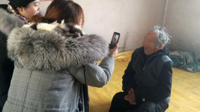 Officials use a cellphone app to photograph people for the facial recognition