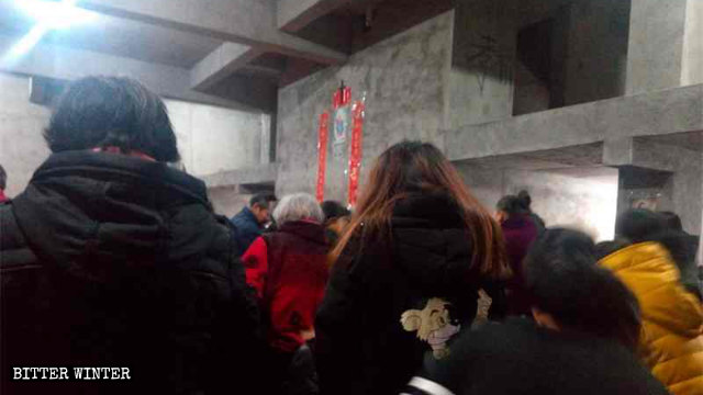 The congregation of Xijia Church attend Mass secretly in an empty house.