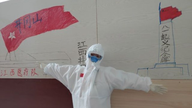 """Medical personnel from Jiangxi Province, sent to help in a modulehospital in Wuhan, the city where the virus started, decorating a wall with images of Jinggangshan to show their resolution to pass on the """"Jinggangshan spirit."""""""