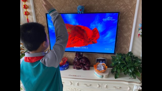 A primary school student gives a salute while watching a flag-raising ceremony on online class through TV at home in Shandong's Jiaozhou city (taken from the Internet).