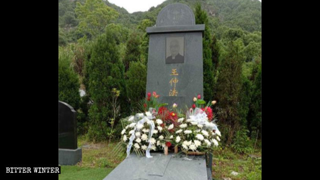 """Chinese characters for the word """"father"""" have been removed from the tombstone."""