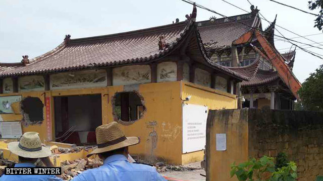 Government-hired workers are demolishing the Fuyuan Temple with an excavator.