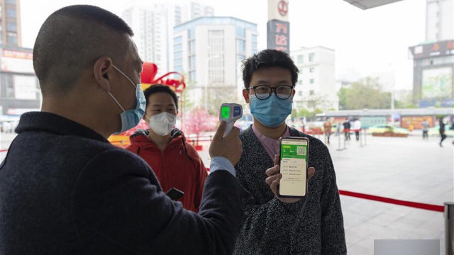 People showing their health codes before entering a shopping mall in Xiangyang, a prefecture-level city in the central province of Hubei.