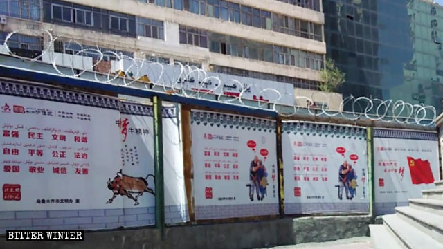 Propaganda posters promote President Xi Jinping's Chinese dream on a wall with barbed wire.